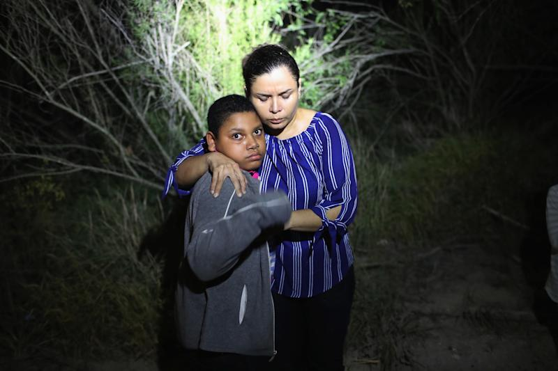 A U.S. Border Patrol spotlight shines on a terrified mother and son from Honduras as they are found in the dark near the U.S.-Mexico border on June 12, 2018, in McAllen, Texas. (John Moore via Getty Images)