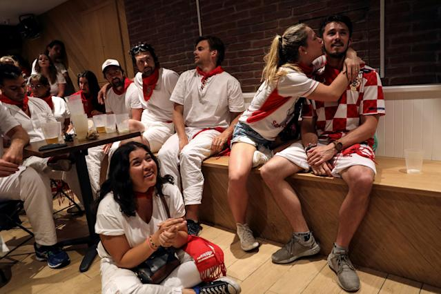 Emily Card, 24, kisses her boyfriend Brad Boulay, 26, as they celebrate Croatia's victory next to supporters of England at the end of the Croatia v England World Cup match, during the San Fermin festival in Pamplona, Spain, July 11, 2018. Even though the couple is from Connecticut, they are Croatian fans because Boulay's grandmother was Croatian. REUTERS/Susana Vera