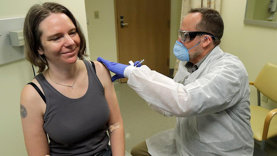 Jennifer Haller, left, smiles as the needle is withdrawn after she was given the first-stage safety study clinical trial of a potential vaccine for COVID-19. Source: AP
