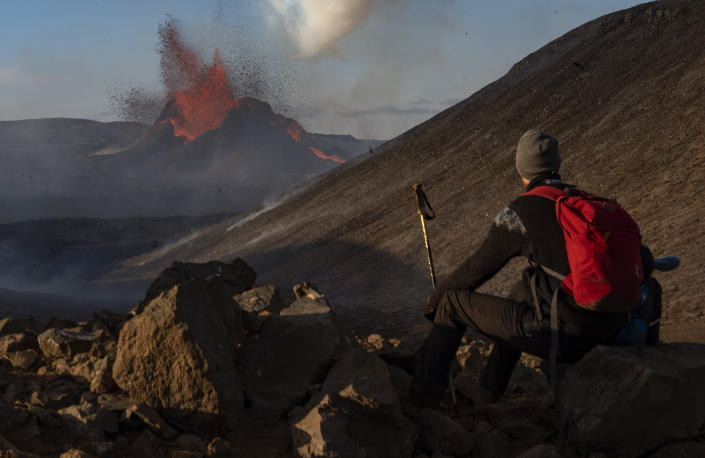 A man watches as lava spews from an eruption of the Fagradalsfjall volcano on the Reykjanes Peninsula in southwestern Iceland on Tuesday, May 11, 2021. (AP Photo/Miguel Morenatti)