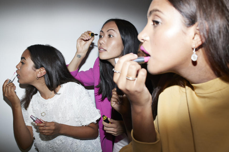 Young women applying make-up while standing together against wall at home