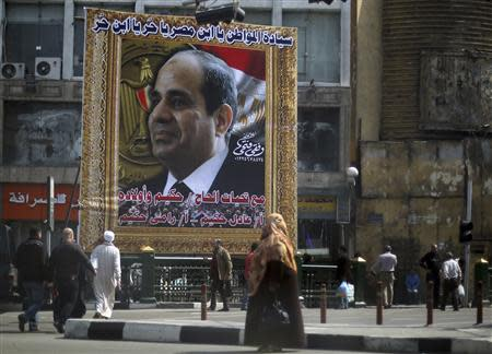 People walk past a huge banner for Egypt's army chief, Field Marshal Abdel Fattah al-Sisi in front of the High Court of Justice in downtown Cairo