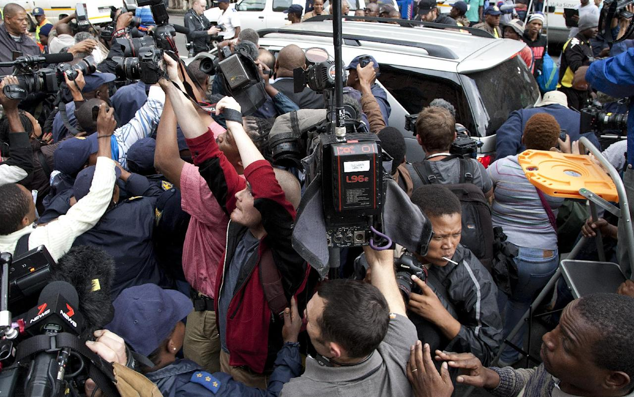 Journalist swamp Oscar Pistorius, as escorted out by his private security and police officers at the high court at the end second day of his trial in Pretoria, South Africa, Tuesday, March 4 2014. Oscar Pistorius is charged with murder for the shooting death of his girlfriend, Reeva Steenkamp, on Valentines Day in 2013. (AP Photo/Themba Hadebe)