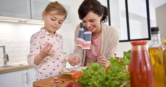 Mom preparing food with her child copyright goodluz/Shutterstock.com