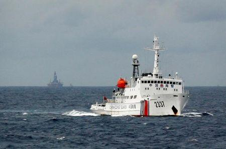 A Chinese Coast Guard vessel (R) passes near the Chinese oil rig, Haiyang Shi You 981 (L) in the South China Sea June 13, 2014. REUTERS/Nguyen Minh/File Photo