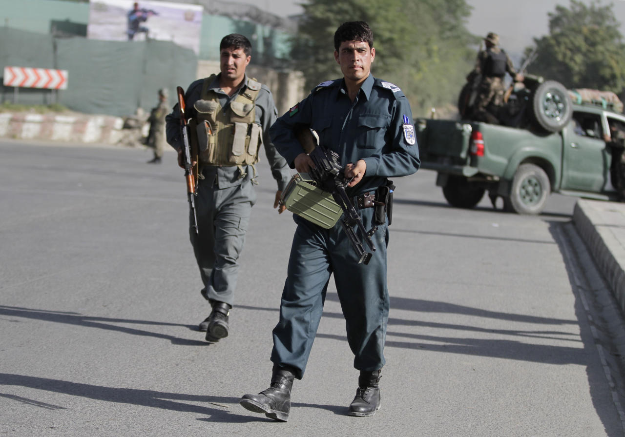 Afghan policemen stand guard near the entrance gate of the presidential palace in Kabul, Afghanistan Tuesday, June 25, 2013 following an attack. Suicide attackers blew up a car bomb and battled security forces outside Afghanistan's presidential palace Tuesday after infiltrating one of the most secure areas of the capital. The Taliban claimed responsibility for the attack that came as reporters were gathering for a news event on Afghan youth at which President Hamid Karzai was expected to talk about ongoing efforts to open peace talks with the militant group. (AP Photo/Ahmad Jamshid)