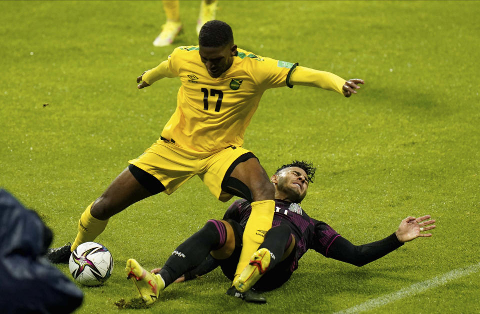 Jamaica's Damion Lowe, left, and Mexico's Ernesto Vega battle for the ball during a qualifying soccer match for the FIFA World Cup Qatar 2022, in Mexico City, Thursday, Sept. 2, 2021.(AP Photo/Eduardo Verdugo)