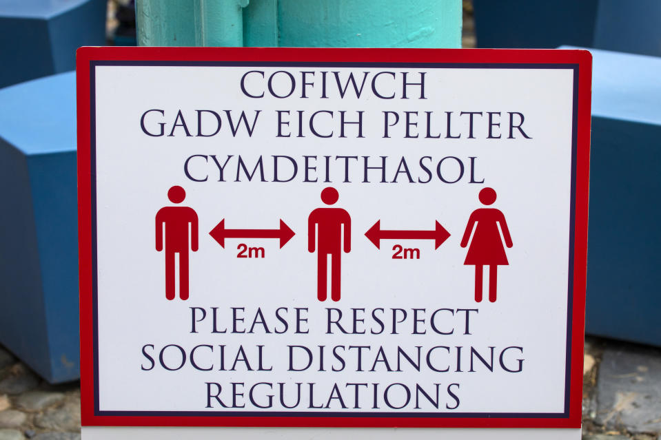 Close-up of a social distancing sign in the village of Portmeirion in North Wales, UK - in both the Welsh and English languages.