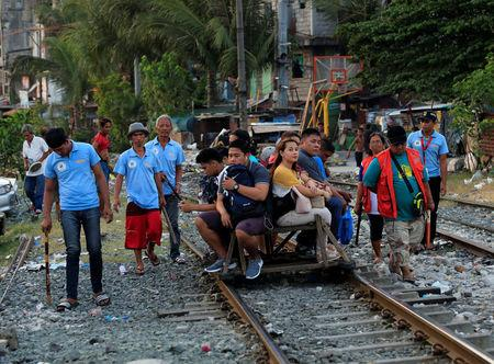 Barangay local security forces which according to the group conducts foot patrol to deter crime and drug abuse in their neighbourhood, carry batons while walking past commuters at a railroad track in Santa Mesa