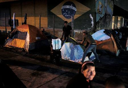 FILE PHOTO: Venezuelan men erect their tent to sleep along the street as they wait to show their passports or identity cards next day at the Pacaraima border control, Roraima state, Brazil August 8, 2018. Picture taken August 8, 2018. REUTERS/Nacho Doce