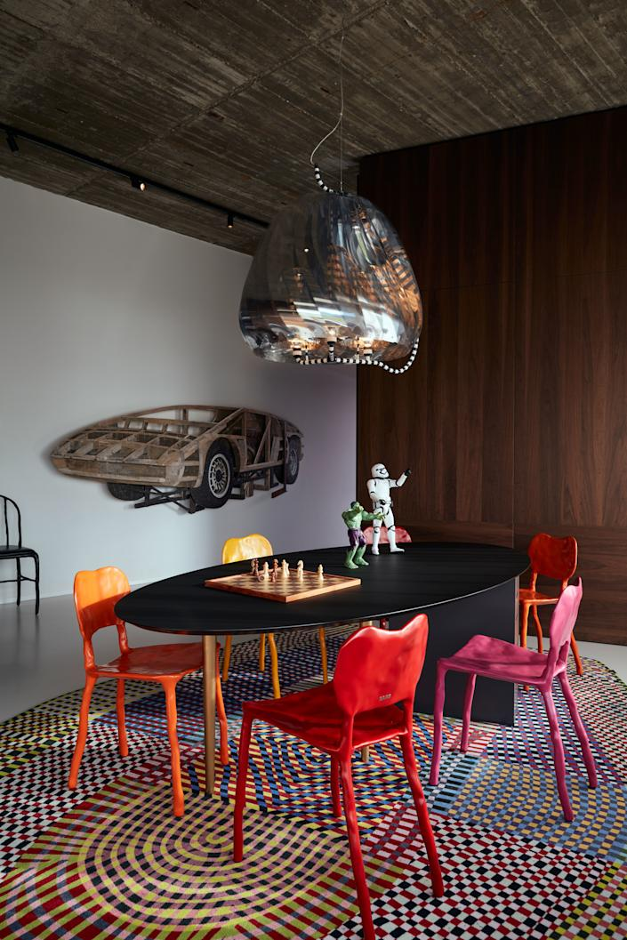 """<div class=""""caption""""> The children's rooms are kept relatively compact in order to create more space for a large communal working space with a TV and gaming corner. The carpet is by Moooi / Bertjan Pot, the Revolving Chandelier is also by Bertjan Pot, the clay chairs are by Maarten Baas, and the hanging artwork is by Ron van der Ende. </div>"""