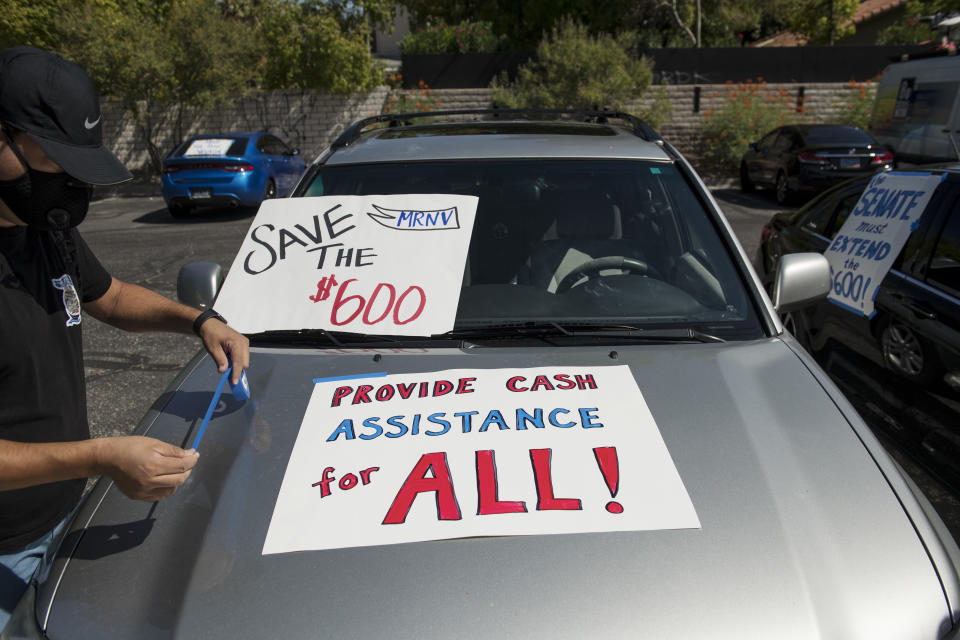 A man tapes signs to his car before participating in a caravan rally down the Las Vegas Strip in support of extending the $600 unemployment benefit, August 6, 2020 in Las Vegas, Nevada. (Photo by Bridget BENNETT / AFP) (Photo by BRIDGET BENNETT/AFP via Getty Images)
