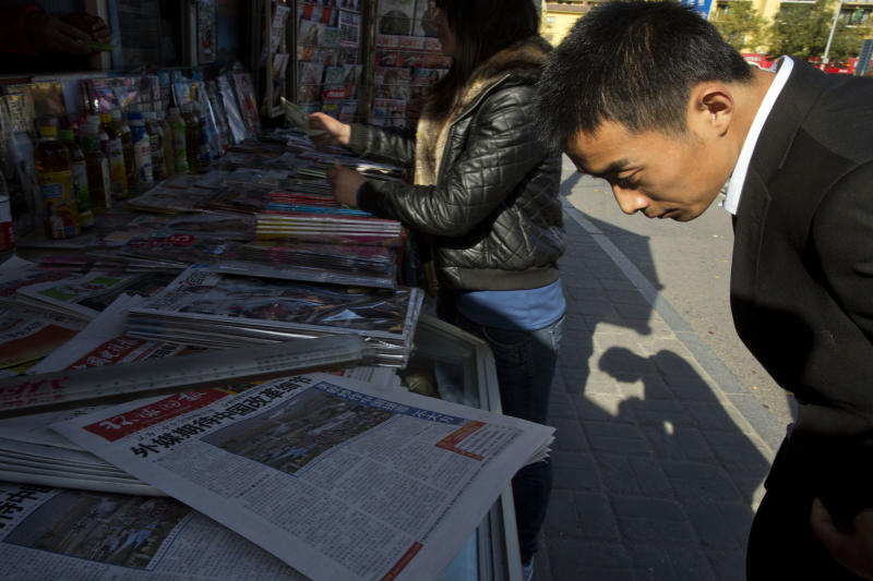 "A man looks over near the front page of a Chinese newspaper showing a photo of the typhoon damage in the Philippines and the white characters on blue which reads ""U.S. and Europe hype up Chinese aid to Philippines as 'Not Generous' "", at a newsstand in Beijing, China, Thursday, Nov. 14, 2013. The outpouring of international aid to the Philippines makes China's contribution for typhoon relief look like a trickle - and that won't help Beijing's campaign to win over neighbors with its soft power. (AP Photo/Ng Han Guan)"