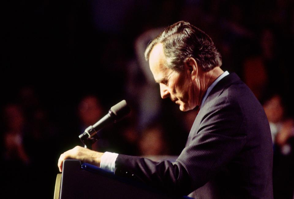 President George H.W. Bush, in profile, stands at a podium