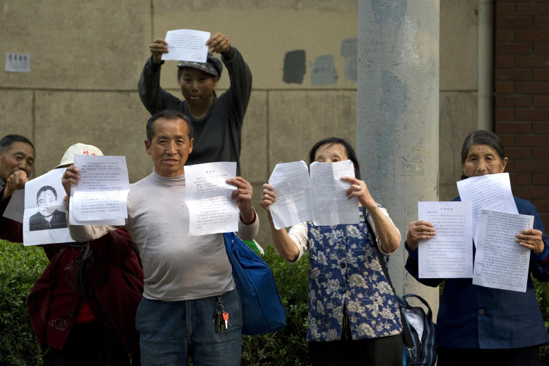 Chinese petitioners hold up papers to attract attentions for their cases outside the hospital where blind activist Chen Guangcheng is staying for treatment in Beijing Monday, May 7, 2012. The Chinese activist who triggered a diplomatic dispute between China and the United States said Monday he was confident that Beijing would hold up its end of a tentative deal to let him study overseas. (AP Photo/Alexander F. Yuan)