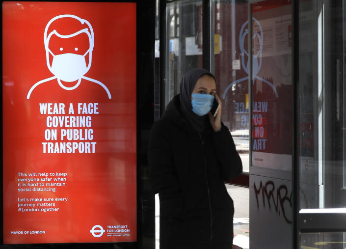 A passenger waits at a bus stop with a sign advising travellers to wear a face covering whilst travelling, in London, Friday, June 5, 2020. It will become compulsory to wear face coverings whilst using public transport in England from Monday June 15. (AP Photo/Kirsty Wigglesworth)