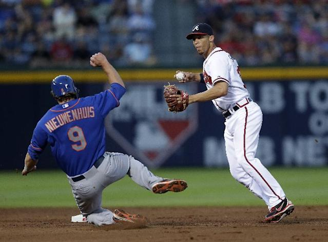 Atlanta Braves shortstop Andrelton Simmons, right, avoids New York Mets' Kirk Nieuwenhuis (9) while turning a double play on an Omar Quintanilla ground ball in the fifth inning of a baseball game on Wednesday, June 19, 2013, in Atlanta. (AP Photo/John Bazemore)