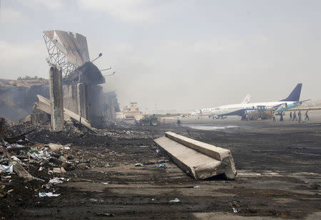 Planes are seen near a section of a damaged building at Jinnah International Airport, after Sunday's attack by Taliban militants, in Karachi