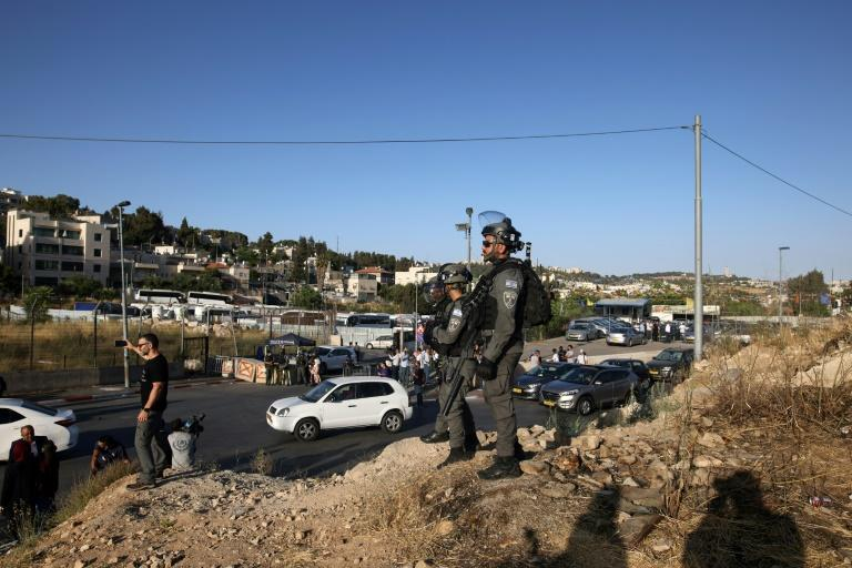 Israeli security forces watch as protesters near an Israeli police checkpoint at the entrance of the Sheikh Jarrah neighbourhood in east Jerusalem on May 29, 2021