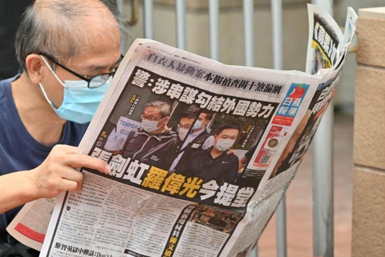 A supporter reads a copy of the Apple Daily newspaper outside a court in Hong Kong