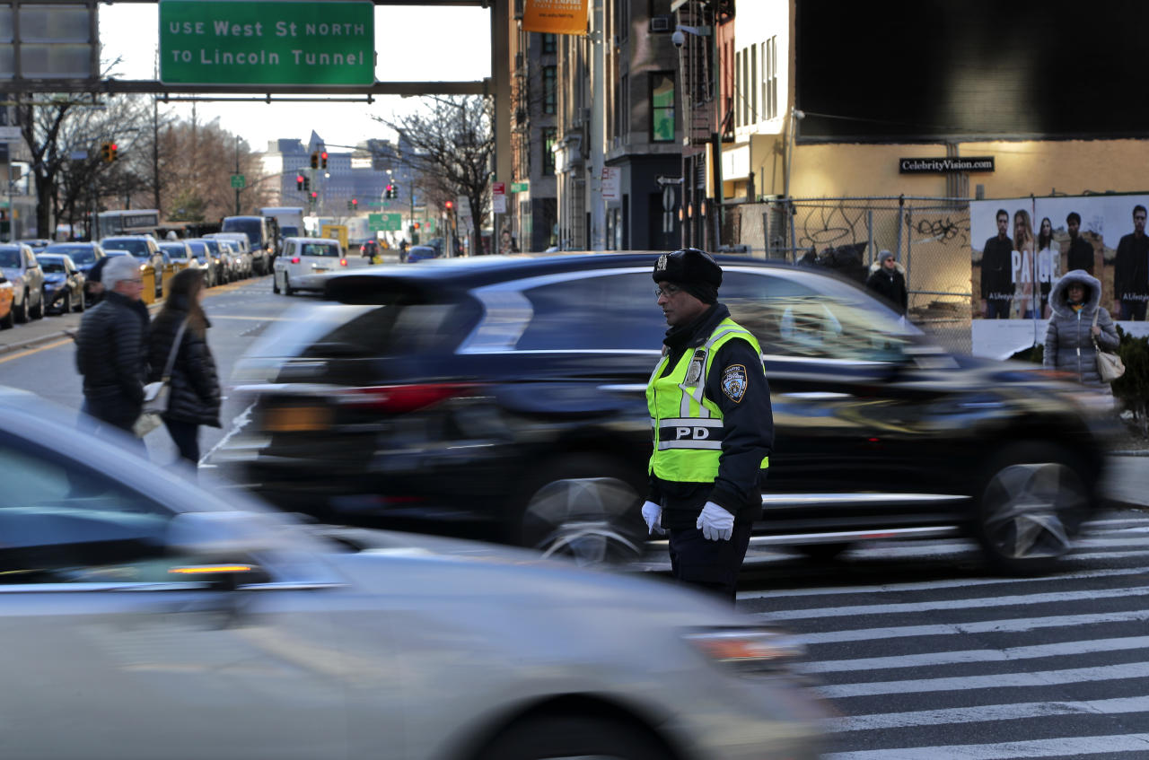 A New York Police Department officer directs traffic during afternoon rush hour at the entrance to the Holland Tunnel, Friday, March 16, 2018, in New York. Prospects appear to be dimming for the latest proposal to impose new tolls on motorists entering the busiest parts of Manhattan. A state panel recommended tolls of as much as $11 or more as a way to address gridlock while raising money for transit. But lawmakers are balking, with some suggesting a more limited fee for taxis, limos and ride-hailing services like Uber instead. (AP Photo/Julie Jacobson)