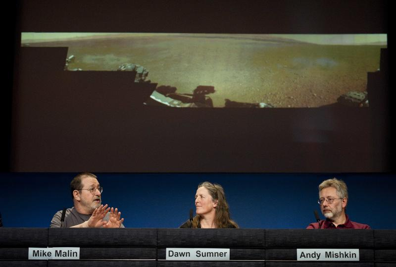 Michael Malin, principal investigator, MastCamera on MSL, Malin Space Science Systems, San Diego, left, talks next to Dawn Sumner, MSL science team member, University of Calif., Davis, and Andy Mishkin, Integratedplanning and execution team chief, JPL, about a low-resolution panoramic image of Mars, background, during an update news conference on Curiosity Mars Rover at NASA's Jet Propulsion Laboratory in Pasadena, Calif., Thursday, Aug. 9, 2012. (AP Photo/Grant Hindsley)