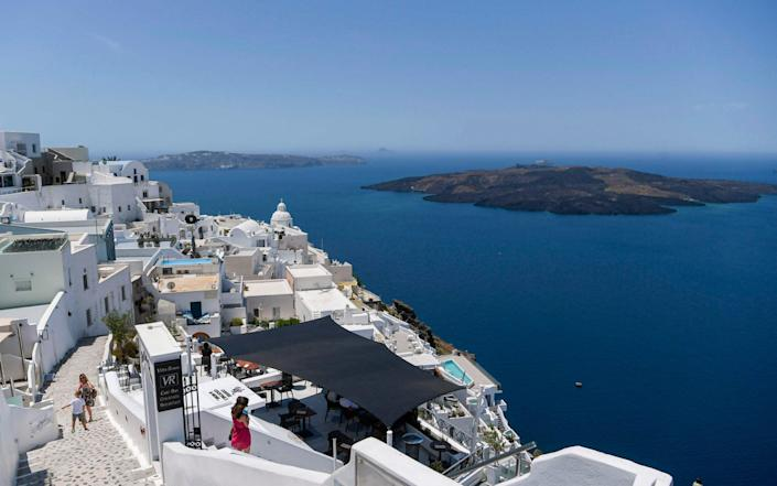 People walk in the empty alleys in the town of Fyra in the island of Santorini on June 14, 2020 as the country prepared for the return of tourists to Greece from around 30 countries by air, sea and land - Aris Messinis/AFP