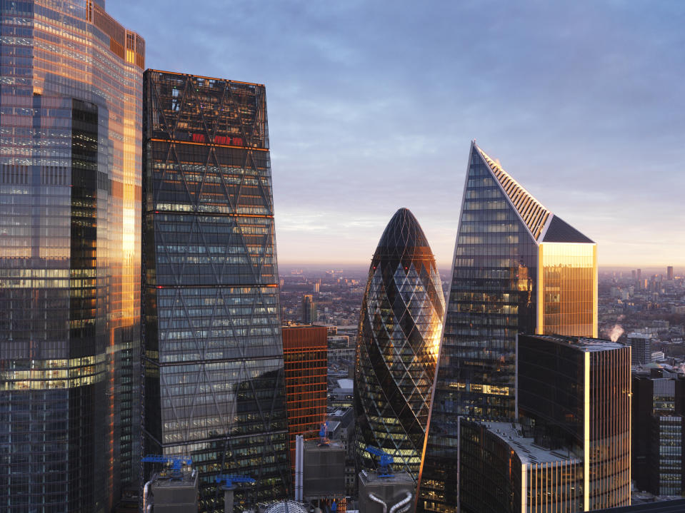 UK, London, elevated view over city financial district skyline looking north illuminated at sunrise
