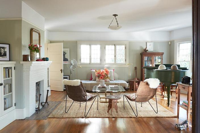 <p>The living room is a mix of classic and modern pieces; the fireplace is original to the house. The midcentury metal and wicker chairs are from the Long Beach flea market, the rug is from Lawrence of La Brea, and the coffee table is from Casa Victoria.</p>