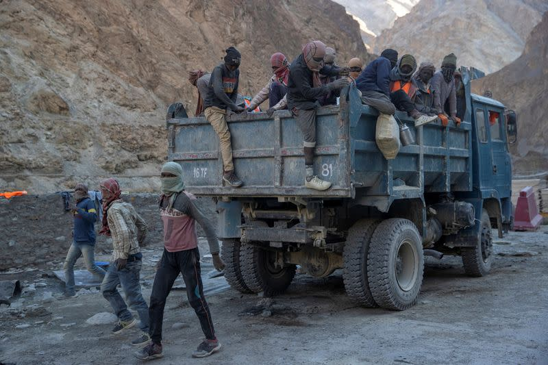 Workers from Border Roads Organisation get off a truck after arriving at their living quarters on an under construction highway in the Ladakh region