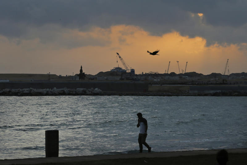 In this July 24, 2019, photo, a Sri Lankan walks by Galle Face, in front of the Chinese-funded sea reclamation project in Colombo, Sri Lanka. Shocks from deadly suicide bombings on Easter Day in Sri Lanka are reverberating throughout its economy in the worst crisis since the South Asian island nation's civil war ended in 2009. The blasts have devastated Sri Lanka's vital tourism industry, source of jobs for many, and hindering foreign investment. (AP Photo/Eranga Jayawardena)