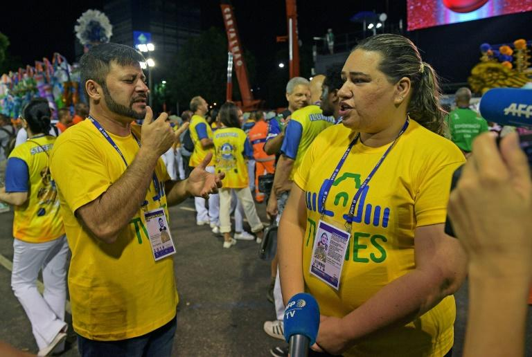 Aulio Nobrega (L) and Daniela Abreu use sign language to communicate during the second night of Rio's Carnival at the Sambadrome in Rio de Janeiro