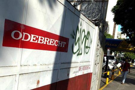 A man walks past the corporate logo of Odebrecht in a construction site in Caracas