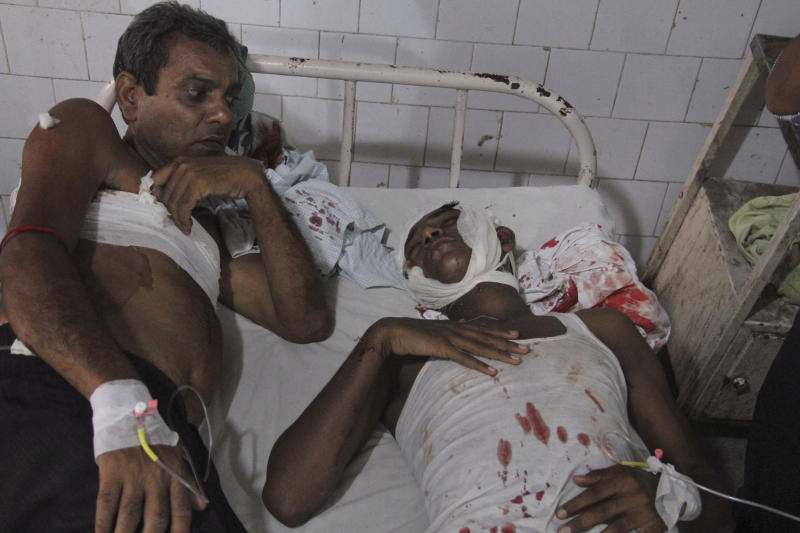 Two men injured in bomb blasts share a cot as they receive treatment at the government medical college hospital in Patna, India, Sunday, Oct. 27, 2013. A series of small bomb blasts killed several people Sunday just hours before a campaign rally by the country's main opposition prime ministerial candidate Narendra Modi. (AP Photo/Aftab Alam Siddiqui)