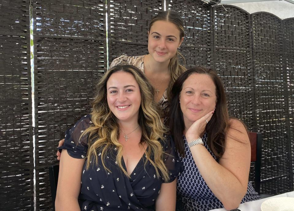 """This undated image shows Traci Cangiano, seated right, with her daughters Daniella, left, and Kristina in the Staten Island borough of New York. The Cangianos, who organized a Facebook group that swapped homemade recipes during the pandemic, have produced a cookbook """"In the Quarantine Kitchen"""" offering some 120 recipes. (Vinny Cangiano via AP)"""
