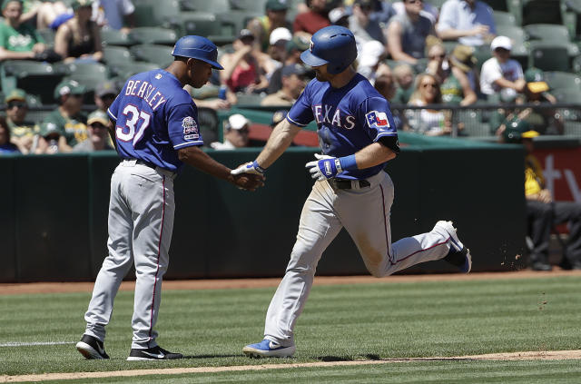 Texas Rangers' Logan Forsythe, right, is congratulated by third base coach Tony Beasley after hitting a solo home run against the Oakland Athletics during the fourth inning of a baseball game in Oakland, Calif., Wednesday, April 24, 2019. (AP Photo/Jeff Chiu)