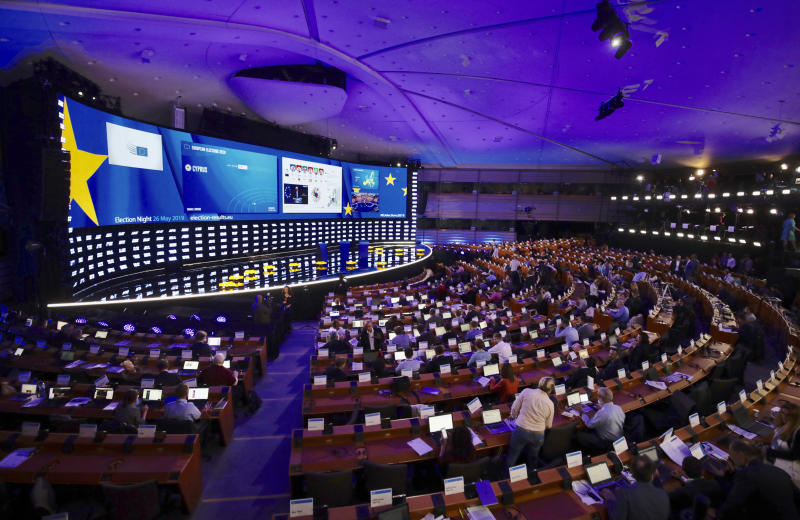 Journalists work in front of the main stage as they cover election night results at the European Parliament in Brussels, Sunday, May 26, 2019. From Germany and France to Cyprus and Estonia, voters from 21 nations went to the polls Sunday in the final day of a crucial European Parliament election that could see major gains by the far-right, nationalist and populist movements that are on the rise across much of the continent. (AP Photo/Olivier Matthys)