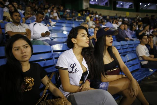 Fans of the Leones de Caracas team watch the opening winter season game between their team and Tigres de Aragua in Caracas, Venezuela, Tuesday, Nov. 5, 2019. The luxury of a night of fun for a couple buying tickets, beer and hotdogs easily cost double the monthly minimum wage equal to the $15 that most Venezuelans earn. (AP Photo/Ariana Cubillos)