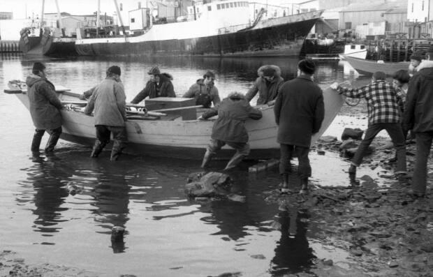 Men in Grand Bank pull a dory ashore after hunting turrs in 1974.