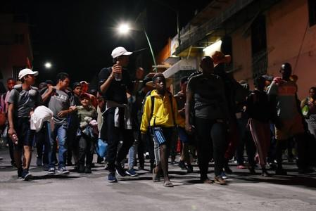Migrants walk along a street in a caravan towards the United States, in Tapachula