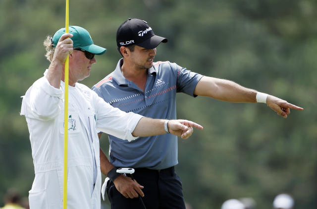 Jason Day, of Australia, talks to his caddie Colin Swatton on the 14th green during the second round of the Masters golf tournament Friday, April 11, 2014, in Augusta, Ga. (AP Photo/Matt Slocum)