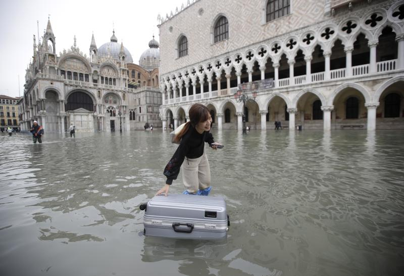 A tourist pushes her floating luggage in a flooded St. Mark's Square, in Venice, Wednesday, Nov. 13, 2019. The high-water mark hit 187 centimeters (74 inches) late Tuesday, Nov. 12, 2019, meaning more than 85% of the city was flooded. The highest level ever recorded was 194 centimeters (76 inches) during infamous flooding in 1966. (AP Photo/Luca Bruno)
