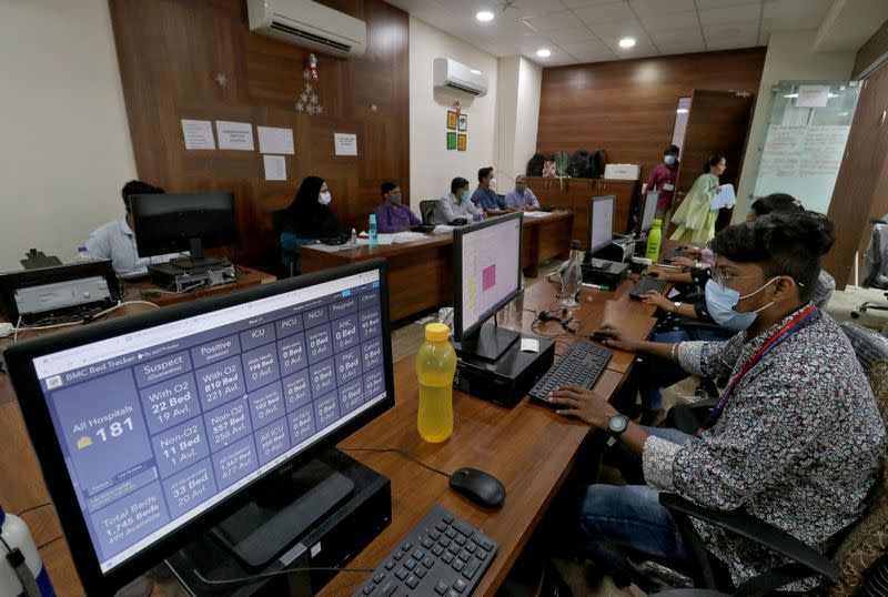 """Volunteers work inside a """"war room"""" set up by BMC to monitor the availability of beds in COVID-19 hospitals across the city, in Mumbai"""