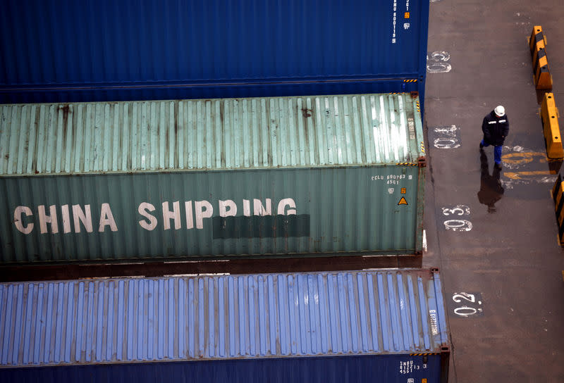 FILE PHOTO: A worker walks past shipping containers at the Port of Shanghai