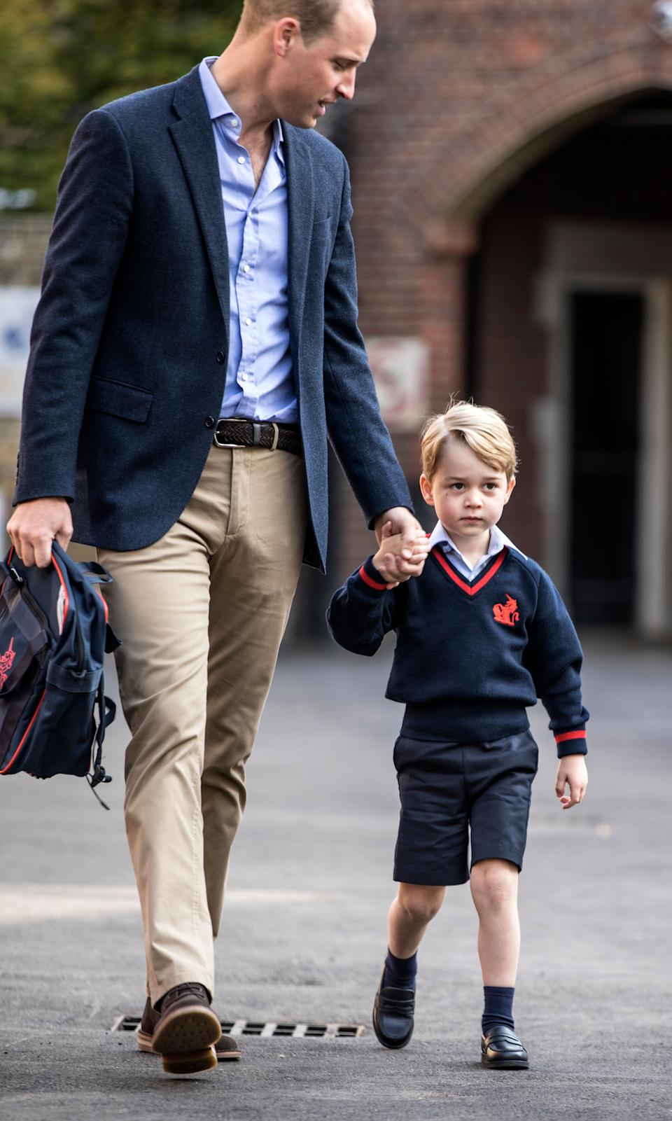 Britain's Prince William, left, accompanies Prince George as he arrives for his first day of school at Thomas's school in Battersea, London, Thursday, Sept. 7, 2017.  Prince William's pregnant wife Kate was too ill with morning sickness Thursday to take young Prince George to his first day of school.  (Richard Pohle/Pool Photo via AP)
