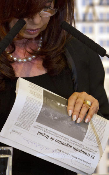 Argentina's President Cristina Fernandez holds a copy of the Spanish newspaper El Pais at Government House where she announced a bill to nationalize Spain's controlled oil company YPF, in Buenos Aires, Argentina, Monday April 16, 2012. Fernandez said in an address to the country that the measure sent to congress on Monday is aimed at recovering the nation's sovereignty over its hydrocarbon resources. The newspaper's headline and subhead read in Spanish: Repsol's Argentine springboard; YPF, cost 13.000 million euros, took the Spanish oil company to the height of the crude business and it represents a third of it's profit. (AP Photo/Natacha Pisarenko)