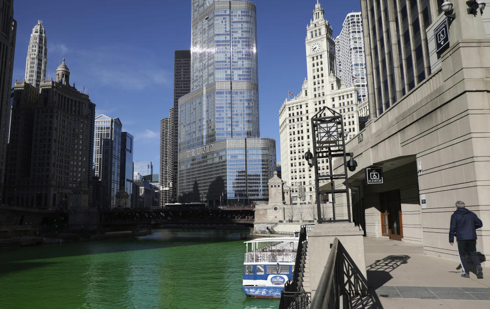 People catch glimpses of the Chicago River dyed green in celebration of St. Patrick's Day on Saturday, March 13, 2021 in Chicago. Mayor Lightfoot sanctioned the famous river dyeing to proceed Saturday, but the Riverwalk was closed to minimize the number of people gathering due to COVID-19. (Abel Uribe /Chicago Tribune via AP)