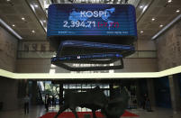 People wearing face masks walk near a screen showing the Korea Composite Stock Price Index (KOSPI) at the Korea Exchange in Seoul, South Korea, Thursday, Oct. 8, 2020. Asian shares were mostly higher Thursday on optimism that U.S. stimulus may be coming, as President Donald Trump appeared to reverse his earlier decision to halt talks on another economic rescue effort. (AP Photo/Lee Jin-man)