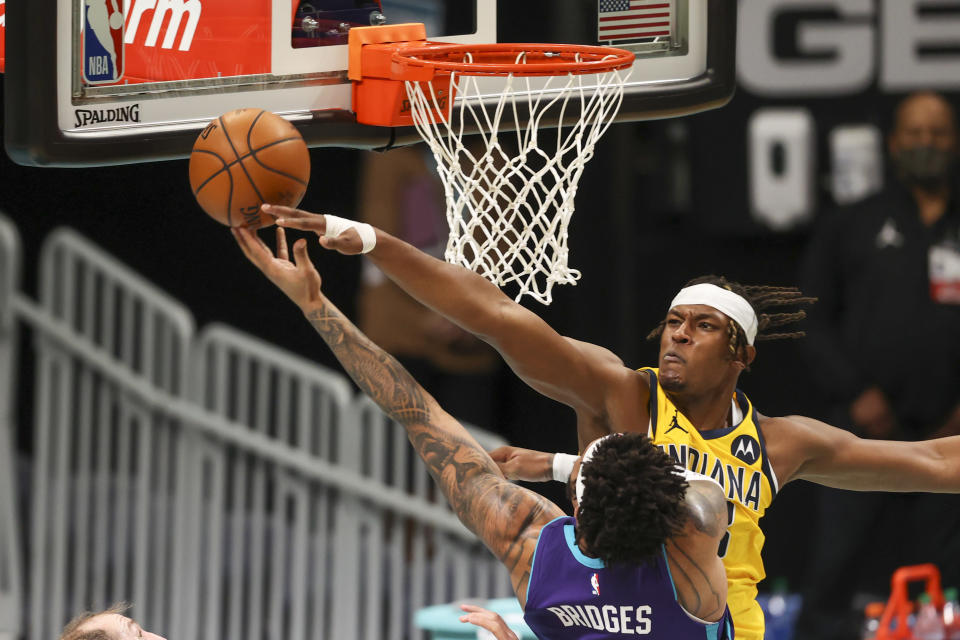 Charlotte Hornets forward Miles Bridges, left, shoots against Indiana Pacers center Myles Turner during the first half of an NBA basketball game in Charlotte, N.C., Wednesday, Jan. 27, 2021. (AP Photo/Nell Redmond)