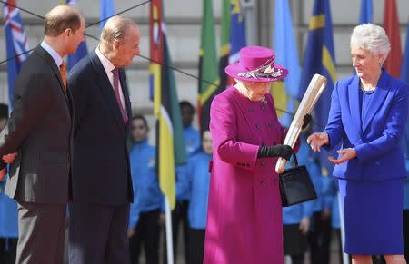 Britain's Queen Elizabeth receives the baton from Louise Martin of the Commonwealth Games organizing committee during the launch of the Queen's baton Relay for the XX1 Commonwealth Games to be held on Australia's Gold Coast next year, on the forecourt of Buckingham Palace in London, March 13, 2017. REUTERS/Toby Melville